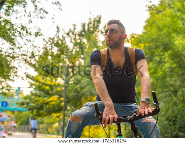 portrait of  young man cyclist, riding a minimalist bike in an urban green setting, from home to work through the park, an ecological and sustainable way to move in the city