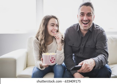 Portrait of a young man and daughter watching TV while eating popcorn on the sofa