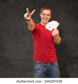 portrait of young man doing a victory gesture playing poker against a grunge wall