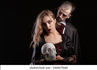 Portrait of young man dressed up like Dracula looking at the neck of his vampire woman. Handsome man and misetrious man dressed up for halloween.