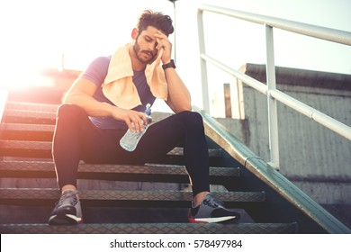 Portrait of young man drinking some water from a bottle while sitting and resting after training.