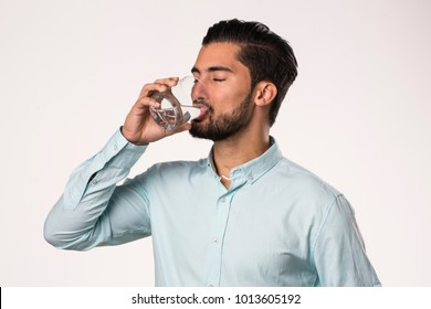 portrait of a young man drinking a water glass
