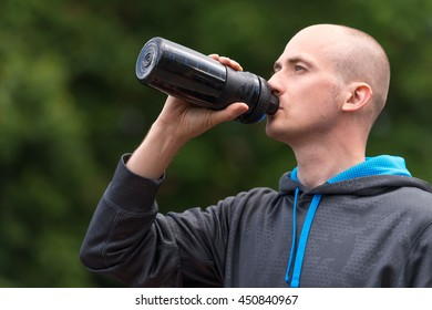Portrait of a young man drinking water during morning jogging in an urban area