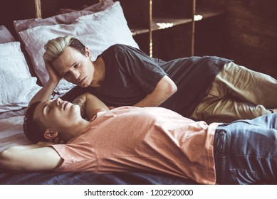 Portrait of young man with dyed hair looking at boyfriend while he sleeping with arms above head