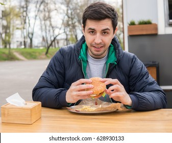 A portrait of young man eating a burger in street food cafe. Fast food eating