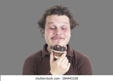 Portrait of a young man eating a muffin