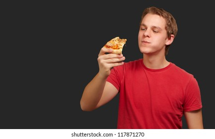 portrait of a young man eating pizza on a black background