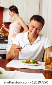Portrait of young man eating salad with his wife cooking on background
