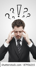 Portrait of a young man with exclamation mark and question marks above his head. Conceptual image of a open minded man. On a gray background