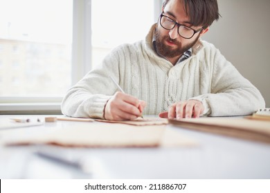Portrait of young man in eyeglasses and white sweater drawing