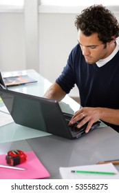 Portrait of a young man in front of a laptop computer