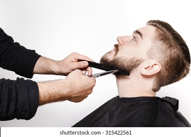 Portrait of a young man getting his beard cut, with scissors and black comb, by a male barber, on a white background, close up