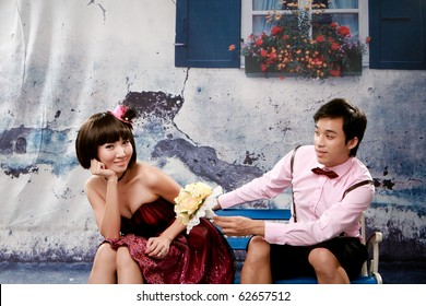 Portrait of young man giving bouquet to young girl in lovely action