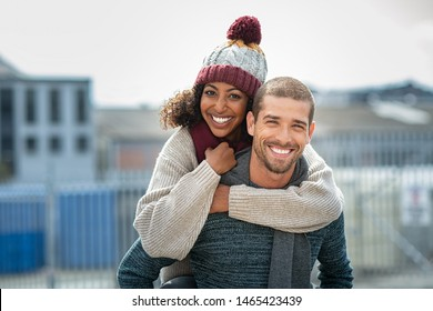 Portrait of young man giving piggyback ride to african woman. Happy boyfriend and smiling girlfriend wearing sweater and wool scarf looking at camera. Multiethnic couple having fun in street in winter