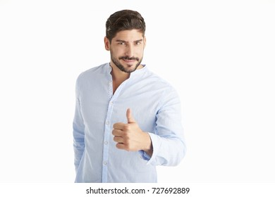 Portrait of a young man giving thumbs up while standing at isolated white background.