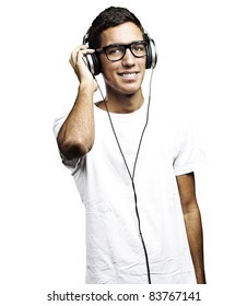 portrait of young man with glasses and headphones listening to music on a white background
