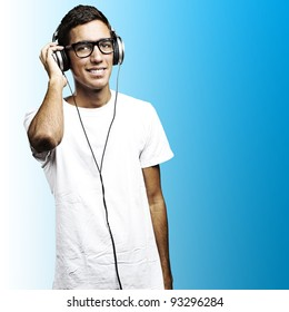 portrait of a young man with glasses and headphones listening to music on a blue background