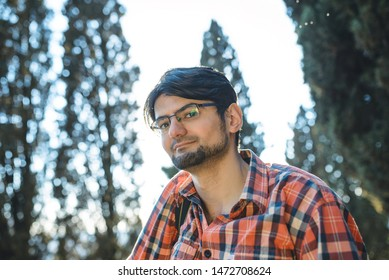 portrait of young man in glasses in park
