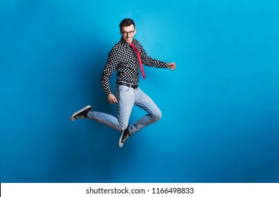 Portrait of a young man with glasses in a studio on a blue background, jumping.