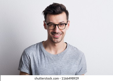 Portrait of a young man with glasses in a studio. Copy space.
