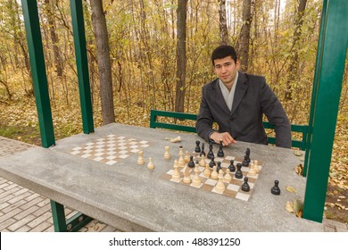 portrait of young man in gray coat over chess table in autumn park