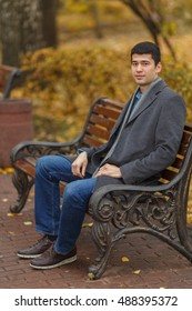 portrait of young man in gray coat and jeans sitting on bench in alley in park