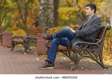 portrait of young man in gray coat and jeans sitting on bench in alley in park, side view