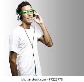 portrait of a young man with green glasses listening to music on a grey background