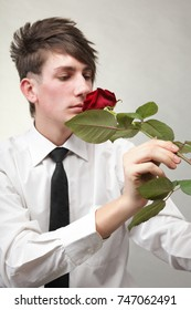 Portrait of a young man grey background. Love and rose.