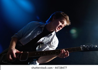 portrait of young man with guitar on dark background