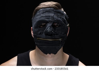 Portrait of the young man in handmade mask on black background