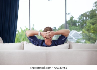portrait of young man with hands behind his head is relaxing on couch