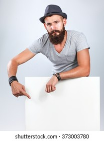 Portrait of young man in hat standing near blank, isolated on white background