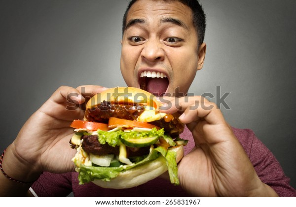 A portrait of young man have a great desire to eat a burger