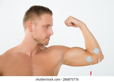 Portrait Of Young Man Having Electrotherapy Of Arm Muscle