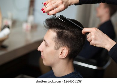 portrait of young man having haircut in barber shop. Hairdresser cutting man's hair with scissors