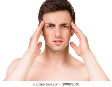 Portrait of young man having a headache while standing over white background.