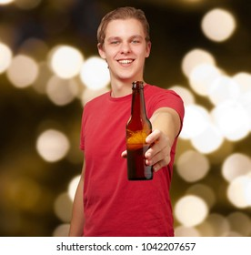 portrait of young man holding beer against a abstract lights