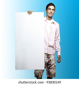 portrait of a young man holding a big white sign against a blue background