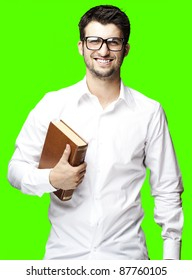 portrait of young man holding book on against a removable chroma key background