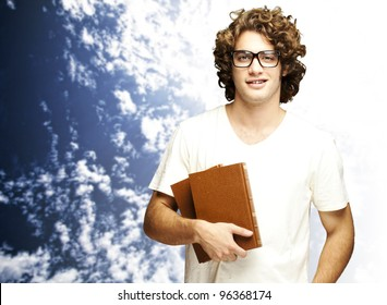 portrait of young man holding books against a cloudy sky background