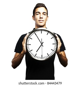portrait of young man holding a clock with his hands over white background