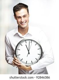 portrait of young man holding clock indoor