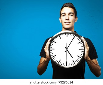 portrait of a young man holding a clock with his hands over a blue background