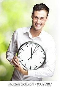 portrait of a young man holding a clock against a nature background