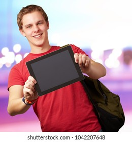 portrait of young man holding a digital tablet against a abstract background