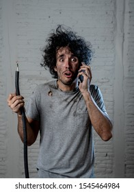 Portrait of young man holding electrical cable after domestic accident with dirty burnt funny face expression calling desperate with mobile phone asking for help. Electricity repairs and DIY concept.