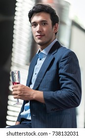 Portrait of young man holding a glass of sparkling rose wine. Handsome chinese single man holding alcoholic beverages with real open air dance club in background. Party concept.