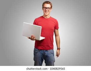 Portrait Of A Young Man Holding A Laptop On Gray Background