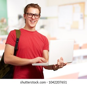 portrait of young man holding laptop and wearing backpack at classroom
